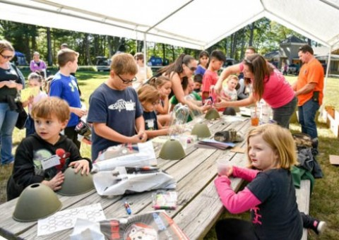 Children are hard at work making bottle rockets at the Scout-O-Rama on Sunday.