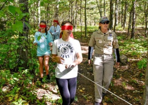 Sunday was Scout-O-Rama day in North Providence, and Pack 5 Leader Allynn Grantham, of North Providence, teaches a lesson in handicap awareness to, front to back, Mia DiDonato, 12, of North Providence, Luccia Rizzo, 12, of North Providence, and her cousin Katharyn Rizzo, 13, of Glocester. (Breeze photos by Charles Lawrence)